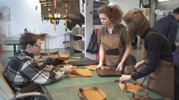 Leather workers making bags details in workshop.