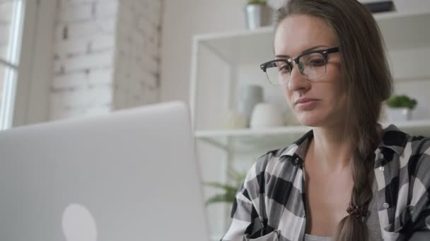 Young business owner female person work with laptop sitting at table in home interior.