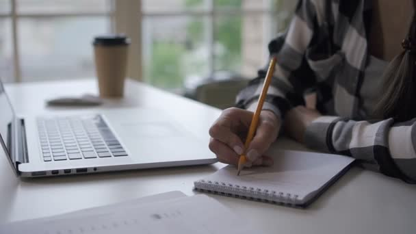 Woman author writing in invest notebook, working at desk with laptop in home office.