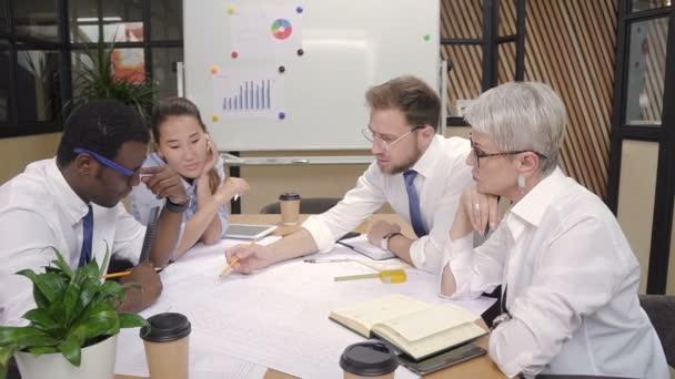 Americká mnohonárodnostní tým hledá při spuštění projektu, práce u stolu v kanceláři osvětlení