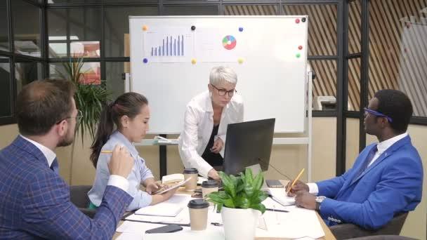 Mnohonárodnostní tým debaty finanční údaje o instruktáž v moderní kanceláři