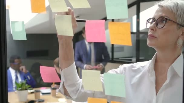 Female boss and businessman in suit putting sticker to glass in office meeting room.