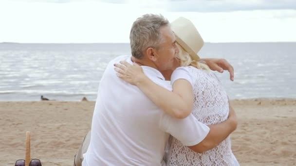 Boldog, érett nő és a nyugdíjas férfi átölelte a tengerparton.