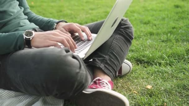 Közelről kezében afrikai főiskolai hallgató szörfözés internet ül a fűben.