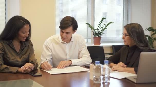 Mnohonárodnostní pár podpisu hypoteční smlouvy v realitní kanceláři.