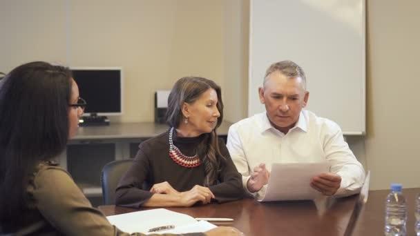 Reife Familie paar Immobilienkauf und diskutieren Hypothek Vertrag mit afroamerikanischen Verkäuferin.