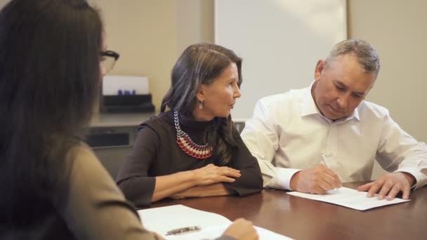 Senior woman Hypothek Vertragsunterzeichnung in Unternehmen Immobilienbüro.