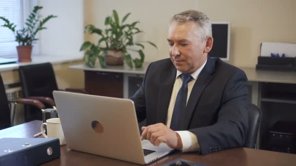 Senior entrepreneur in suit working on laptop computer in office.