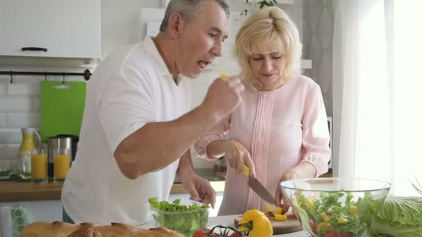 Elderly family couple cooking salad for lunch together in kitchen.