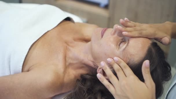 Adult woman is lying on massage table and getting professional, medical, energy procedure.