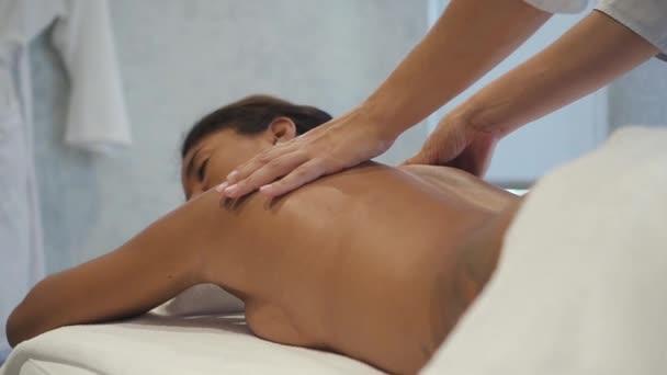 Professional terapist massaging shoulders of african woman in spa salon.