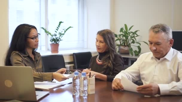 Senior businessman and mature businesswoman discussing contract details in lawyer office.