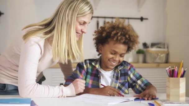 Kreativní a chytré dítě sedí u stolu a dělá si domácí úkoly.