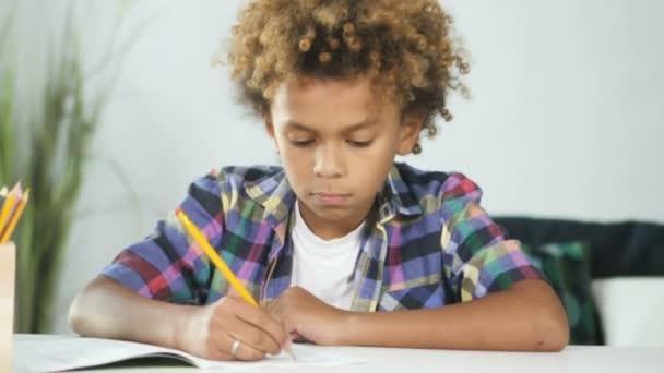 Afro-amerikai fiatal fiú ül az ebédlőasztalnál, és ezzel iskolai házi feladat.