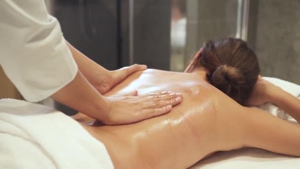 Atraktivní mladá žena leží u masážního stolu a dělá omlazací lékařskou péči.