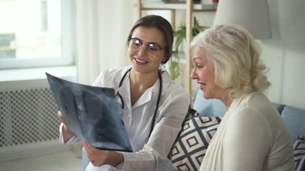 zufriedener Arzt besucht ältere Dame und bespricht Röntgenbild