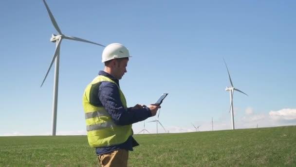 Technikus közelében álló szélmalom és monitoring rendszer asztaliten
