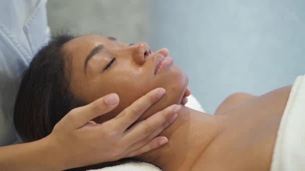multiethnische ruhige junge Frau bekommt medizinische Gesichtsmassage von professioneller Hand.