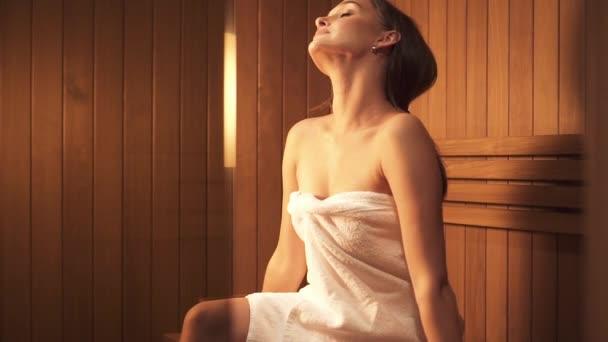 Frau sitzt auf Holzbank im Saunabereich