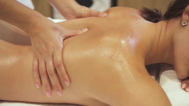 Kezét professzionális masszázs terapeuta térdelő vissza a nő üdülőközpont.