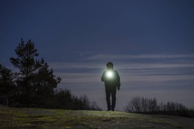 Man standing outdoor at night in forest shining forward with flashlight
