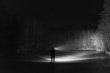 Man standing outdoor at night in forest shining forward with flashlight. Nice strong light beam. Beautiful abstract photo. Calm, peaceful and mystical image.