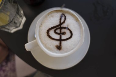 Close up photo of white cup with coffee and milk. Nice detail of musical note in the cream. Good and tasty drink.