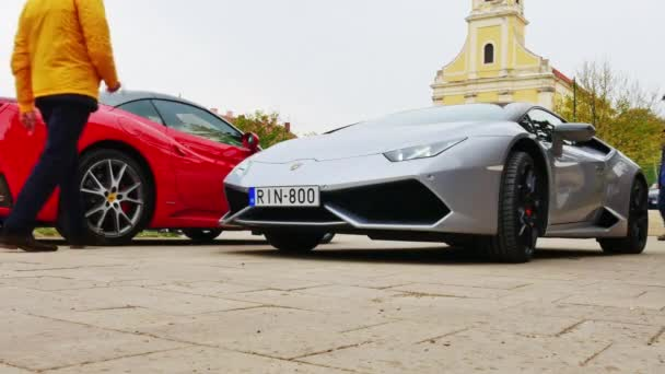 VARPALOTA, MAĎARSKO - 13. dubna 2019: Pohled na sportovní vůz Lamborghini, který pomalu projíždí kolem Ferrari ve Varpalotě v Maďarsku na akci Italské dny..