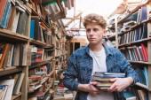 Fotografie Mladý student chůzi v knihovně s knihami ve svých rukou a hledal literaturu. Portrét pohledný mužů na výběr knih v knihovně staré