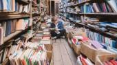 Mladý muž sedí na podlaze v staré knihovny veřejné a čtení knih. Pojem učení. Student bude zabírat sebevzdělávání v knihovně
