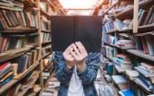 Fotografie Mladý muž stojí v útulném, staré, veřejné diskuze a drží knihu před obličejem. Student se zavře knihu s obličejem. Face kniha