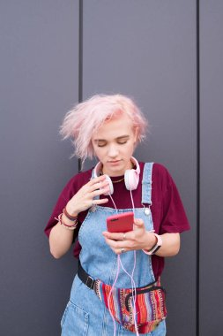 The sweet hipsters girl with stylish clothes, colored hair and headphones is in a dark background and uses a smartphone. Creative girl against the background of a dark wall.