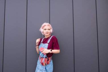 Sweet smiling girl with pink hair and pink headphones listening to music on the background of a dark wall. Cute girl listens to music in the headphones on the background of a gray wall and smiles.