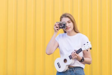 Pretty girl with a ukulele in hand makes the photo on the retro camera. Hipsters do a ukulele and a film camera on a yellow background.