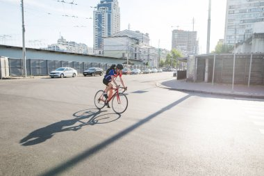 Cyclist in a helmet and athletic dress rides on a red bicycle road. A cyclist moves around the city on a city bike. An athlete riding a bike on the road. Sports concept