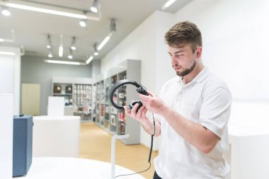 Buyer stands in the technology store and looks at the headphones. A handsome man buys headphones in a modern electronics store. Buying headphones.