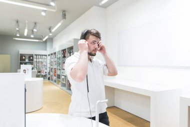 Handsome man in a white T-shirt tests headphones in a modern tech store. Buyers listen to music in headphones against the background of an electronics store. Select and buy headphones.