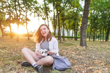 smiling stylish girl sits in a park, plays on a white ukulele and looks at the camera. The happy girl is a musician playing ukulele and sings outdoors.