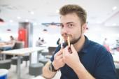 Fotografie Legrační muž s bradkou vložen hranolky místo zuby a vypadá na kameru. Zábavná osoba jíst hranolky v restauraci rychlého občerstvení. Hrát si s jídlem