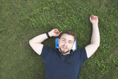 Handsome man with a beard lays on a green lawn on books under his head, looks at the camera and smiles. Happy student lays a green grass books under his head. Rest from studying