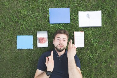 Portrait of a man lying on the grass near the books and looking into the camera. Student lays on the grass with books near the head. Rest on campus after studying. Top view