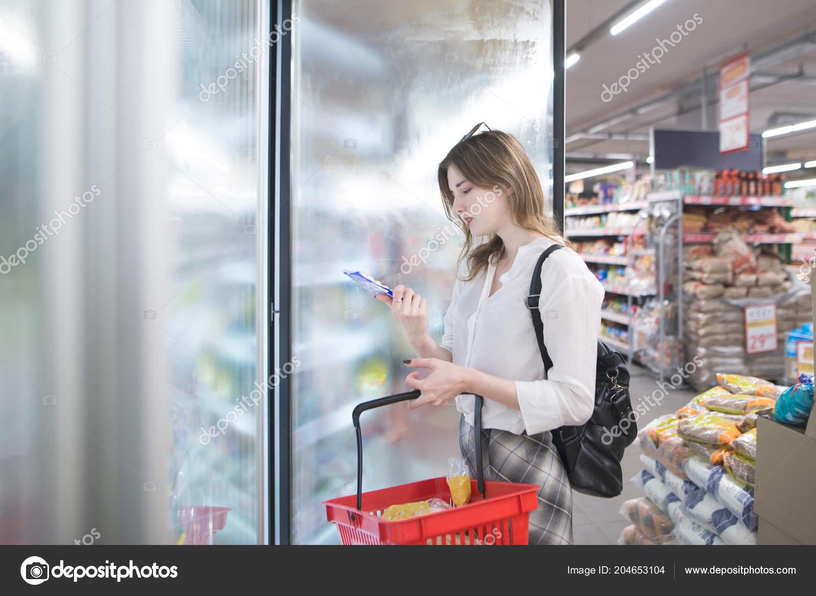 Kühlschrank Korb : Attraktive junge frau steht den kühlschrank das geschäft mit