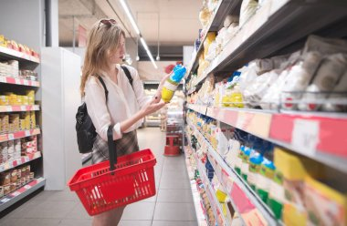 Stylish young girl standing in a grocery supermarket in her arms and reading a label. Female buyer selects products in a supermarket.