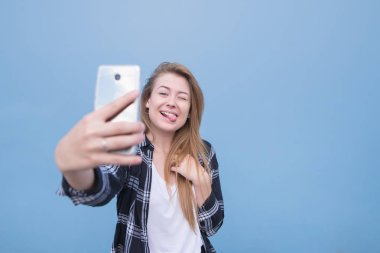 Positive young woman posing and doing a selfie on an isolated blue background. Happy girl picks up herself on a smartphone.