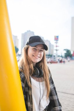 Stylish portrait of a girl in casual clothes and headphones standing on the background of the city, looking into the camera and smiling. Street style