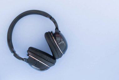 Wireless headphones are isolated on a blue background, the top view. Musical concept. Copyspace