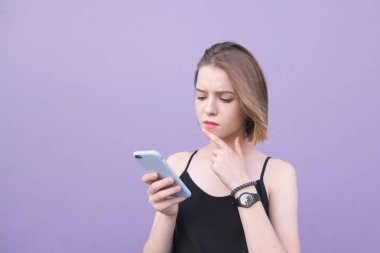 Beautiful young girl standing on a purple background and looking at a smartphone with a thoughtful look. Portrait of a cute girl with a smartphone
