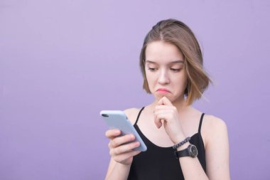 Sad girl stands on a purple background and uses a smartphone. Pretty girl with a sad face looks at a smartphone on the background of a purple pastel wall.