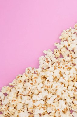 Popcorn scattered at half the pastel pink background and a space for copyspace. Popcorn on a red background. Flat lay. Copyspace. Cinema Concept.