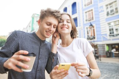 Happy couple listening to music in one headphone for two. Happy young man with a glass of coffee in his hands, girl with a smartphone, walking around the city and listening to music in the headphones.
